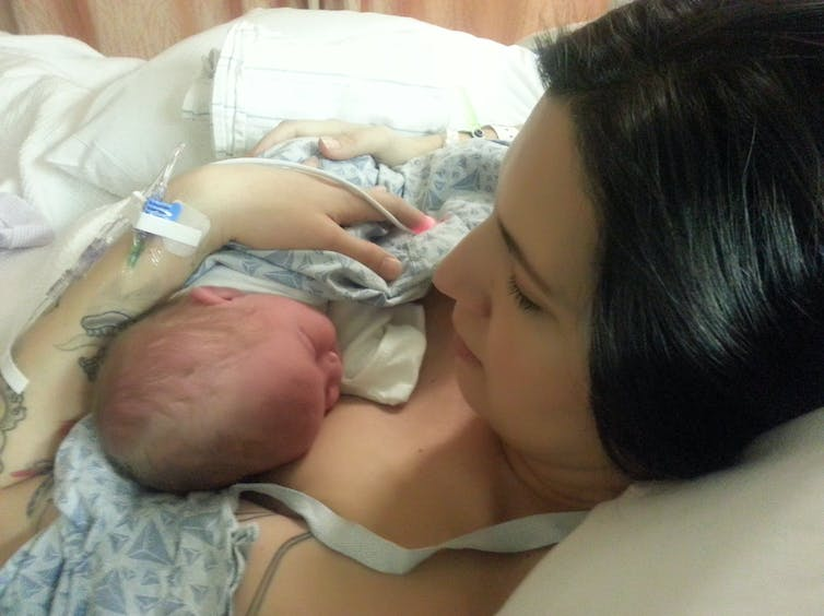 A woman looks at a newborn baby in her arms