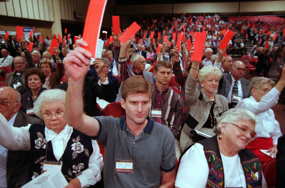 Voters raise their orange ballots to reject the Southern Baptist Convention's call for women to ``submit graciously'' to their husbands, during the Baptists General Convention of Texas held in El Paso, Texas. November 9,1999