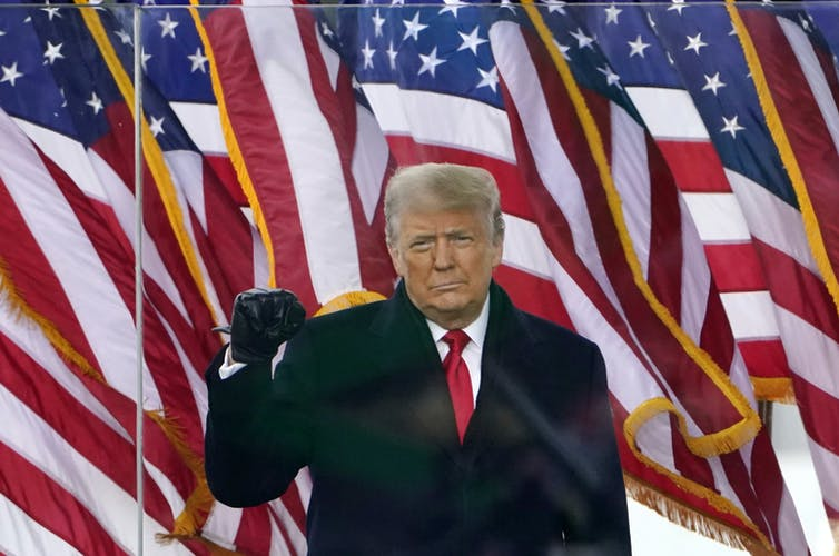 Donald Trump wearing a dark overcoat and standing in front a bunch of American flags holds up his fist.