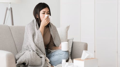 A young woman sits on the couch wrapped in a blanket, blowing her nose.