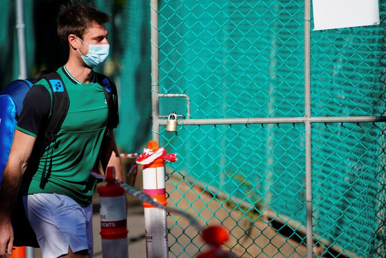 A tennis player undergoing mandatory quarantine enters a restricted training area in advance of the Australian Open in Melbourne, Australia
