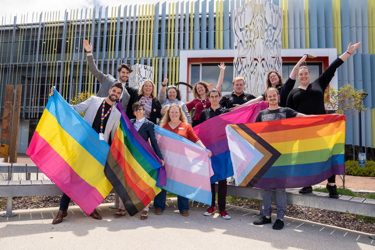 ECU staff and students hold up the pansexual flag, rainbow flag, trans flag, bisexual flag and progress pride flag with their hands waving in the air and smiling.