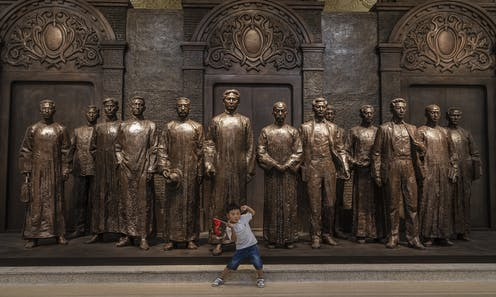 A young boy poses in front of 13 statues depicting the founders of the Chinese Communist Party in Shanghai, 1921.