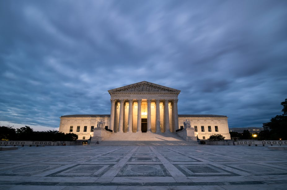 The supreme Court is lit up under an overcast sky.