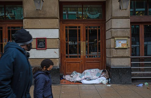 A mother and son wearing masks walk past a homeless person sleeping in front of a doorway