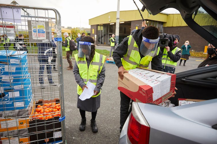 Marcus Rashford and his mother wear hi-vis vests and COVID face shields while loading food into cars at a food bank