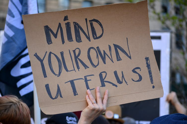 Protester holding up sign that says 'mind your own uterus!'
