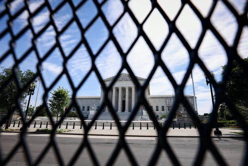 The U.S. Supreme Court is seen through security fencing