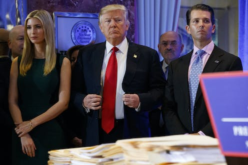 Donald Trump stands between his daughter Ivanka and son Donald Jr. at a news conference in a hotel lobby with Allen Weisselberg's head peaking out behind them.