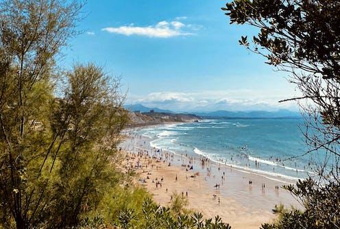 Photo d'une plage peuplée, avec une mer calme agitée par quelques vagues