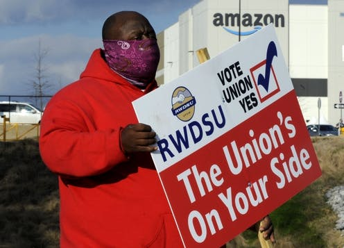 A Black man in a red coat and a purple face mask holds a pro-union sign outside of an amazon facility