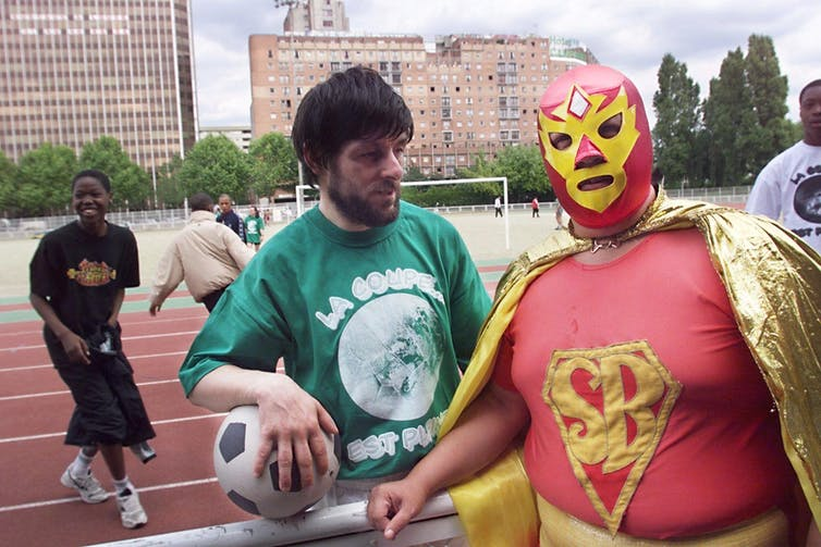 A man holding a soccer ball stands next to a man wearing a red full-face mask with a cape and an 'SB' emblem on his shirt.