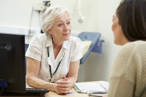 GP talks to patient in a consulting room.