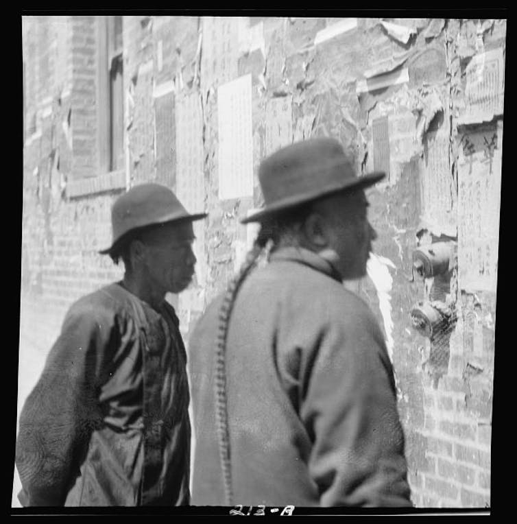 An archive photo depicting two men reading a notice in Chinatown