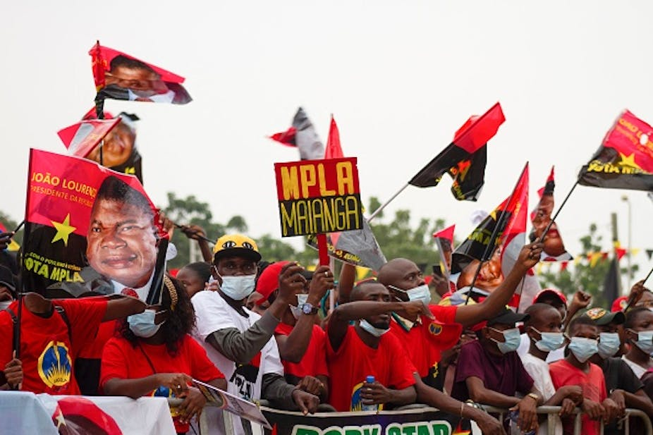 People wearing COVID-19 masks wave Angolan flags and those bearing the face of President João Lourenço.