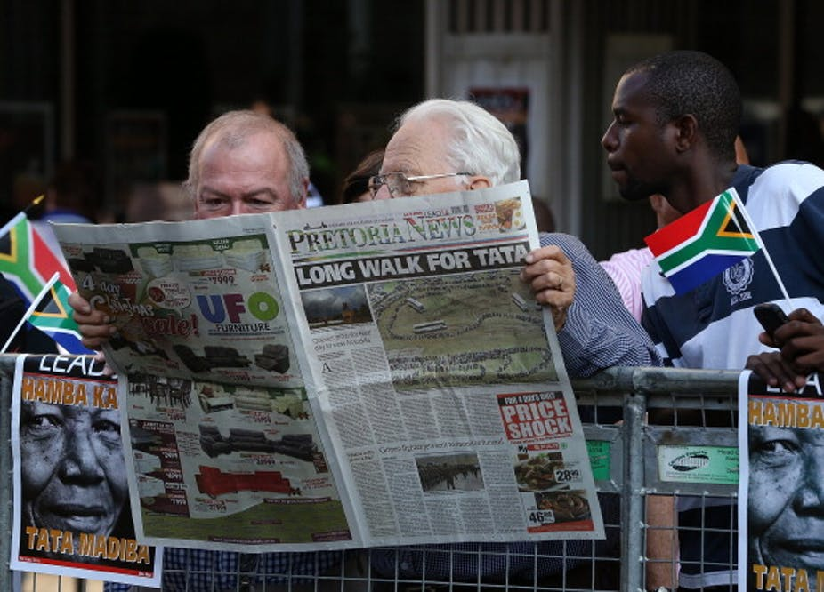 A young man holding a miniature South African flag in his left hand, reads a newspaper over the shoulders of two balding, elderly men.