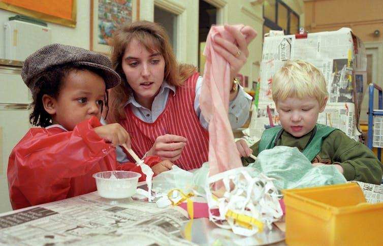 Une enseignante d'âge préscolaire brandit un morceau de tissu lors d'une séance d'artisanat avec deux garçons en tablier
