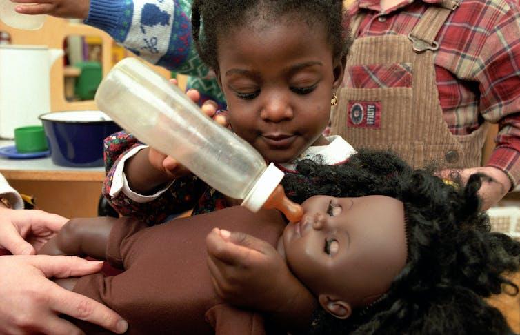 Une petite fille joue avec une poupée et un biberon