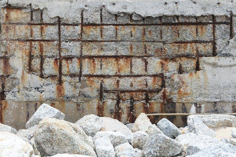 Hormigón reforzado que se desmorona exponiendo la rejilla de acero oxidada.