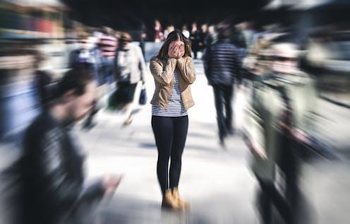 Jeune femme en état de panique dans une foule