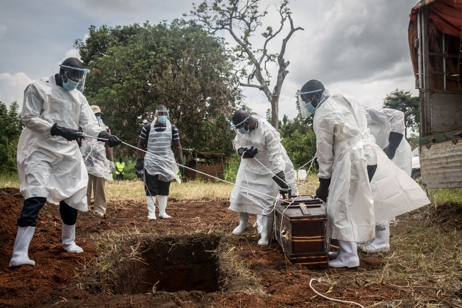Health workers wearing protective suits lower the body of a COVID-19 victim for burial at a graveyard in Gulu, northern Uganda.