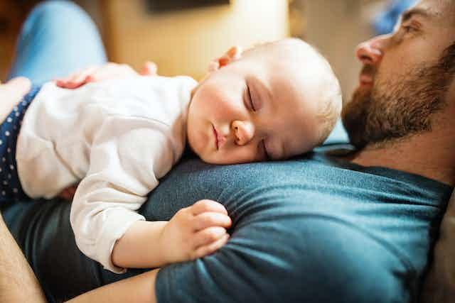 Un bébé endormi dans les bras d'un homme