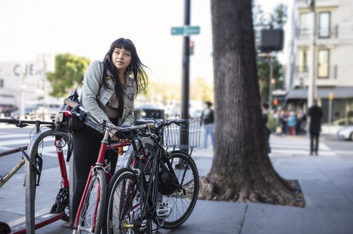 On a busy city sidewalk, one Latina leans over to lock her bike before heading into work. She's dressed casually with denim jacket and black jeans, a shoulder bag hangs from one shoulder. There are two other bikes in the rack already. A slight breeze lifts her long dark hair and we see dozens of pedestrians in soft focus in the background waiting at a crosswalk. A very old tree trunk stands tall and strong next to the bike rack, roots lifting the pavement in this place where nature and city come together in balance.