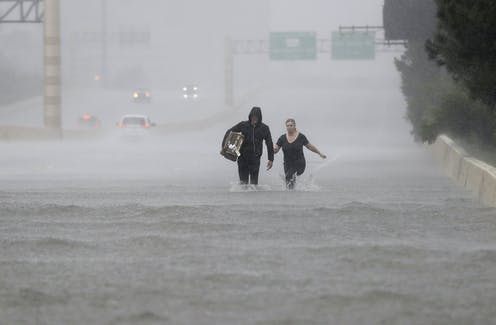 A man and woman walk through knee-high water on an highway in the rain.