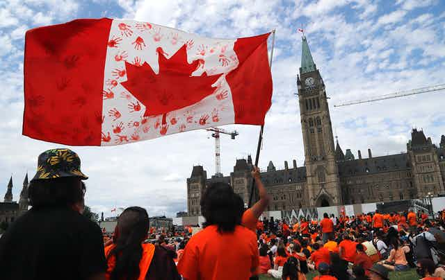 Protesters wave a Canadian flag imprinted with the hand prints of children in red.