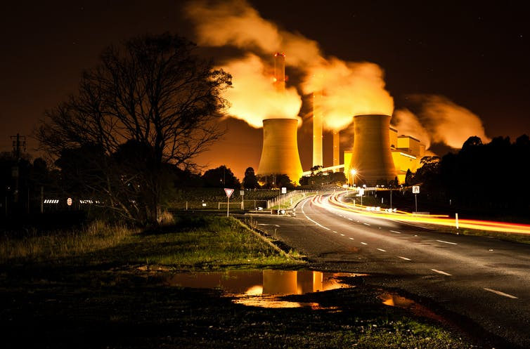 Coal-fired power station at the end of a road, at night