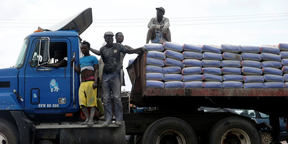 Men standing on a truck loaded with bags