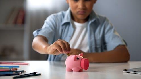 Boy putting coin in piggy bank.