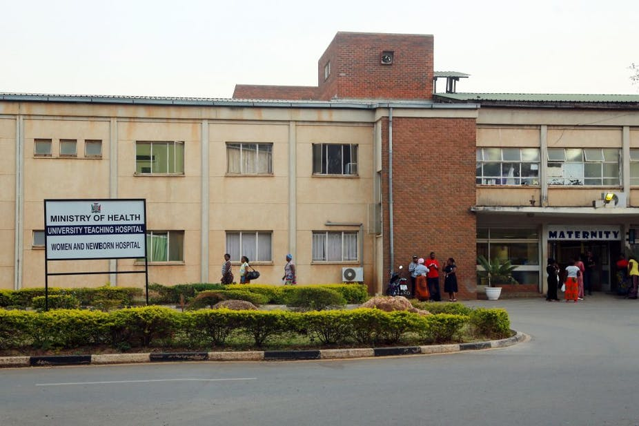 Outside of a hospital with a sign and people standing.