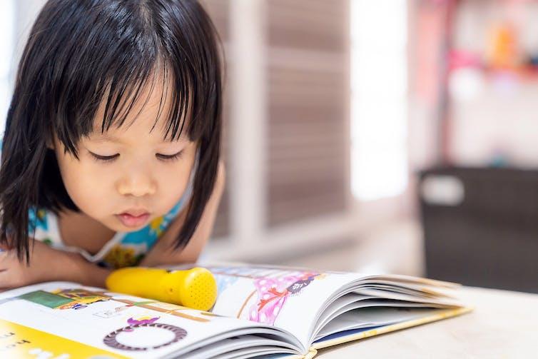 A young girl pores over an activity book
