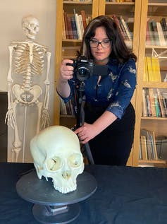 A researcher holding a camera takes a photo of a skull — a skeleton and a bookcase in the background