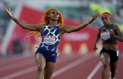 Richardson stretches both arms and lifts her hands after crossing the finish line