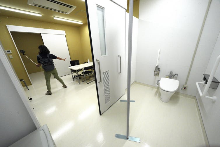 A sectioned-off room with white walls, a sliding door, and a urinal.