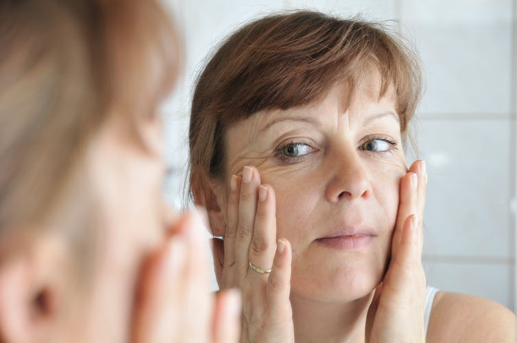 Woman in her 40s looks in the mirror and stretches her wrinkled skin.