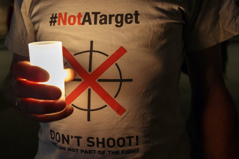 Person wearing a T-shirt with the slogan Not A Target holds a candle or torch