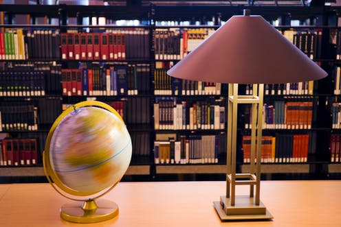 Globe and lamp on a table, with shelves of books in the background
