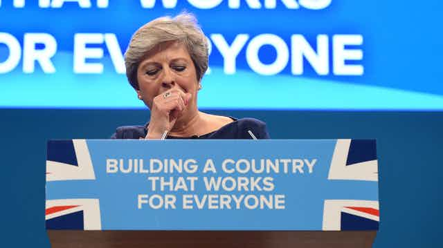 Theresa May, then the UK prime minister, coughs uncontrollably during a speech at the Conservative Party conference in October 2017.