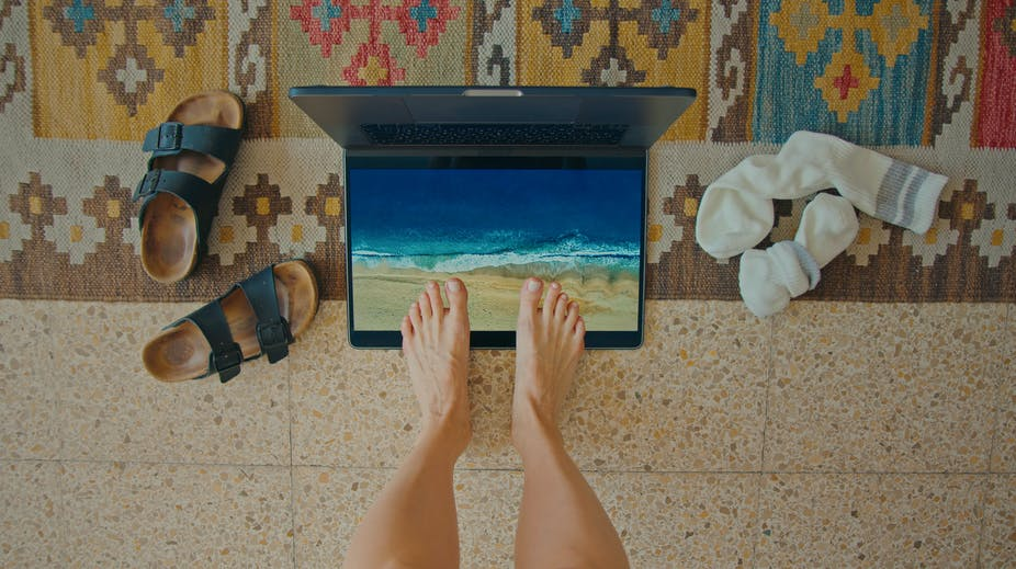 Feet standing on laptop screen showing beach scene with shoes and socks discarded on the floor on either side