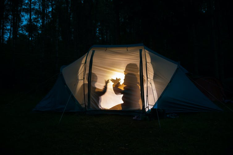 Silhouettes of people making shapes by a light in a tent at night