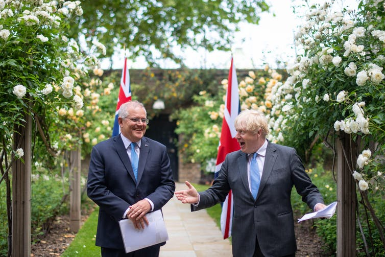 Boris Johnson and Scott Morrison in a garden having a joke