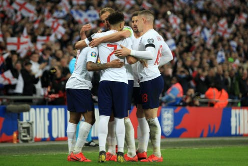 Five of England's players embrace after scoring during a qualifying Euros match