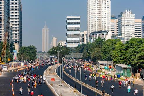 Crowds of pedestrians walk down an empty dual carriageway in central Jakarta