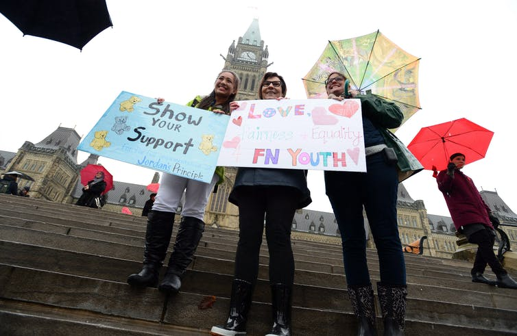 People stand in front of parliament hill holding signs 'Show your support' and 'Love First Nations Youth'