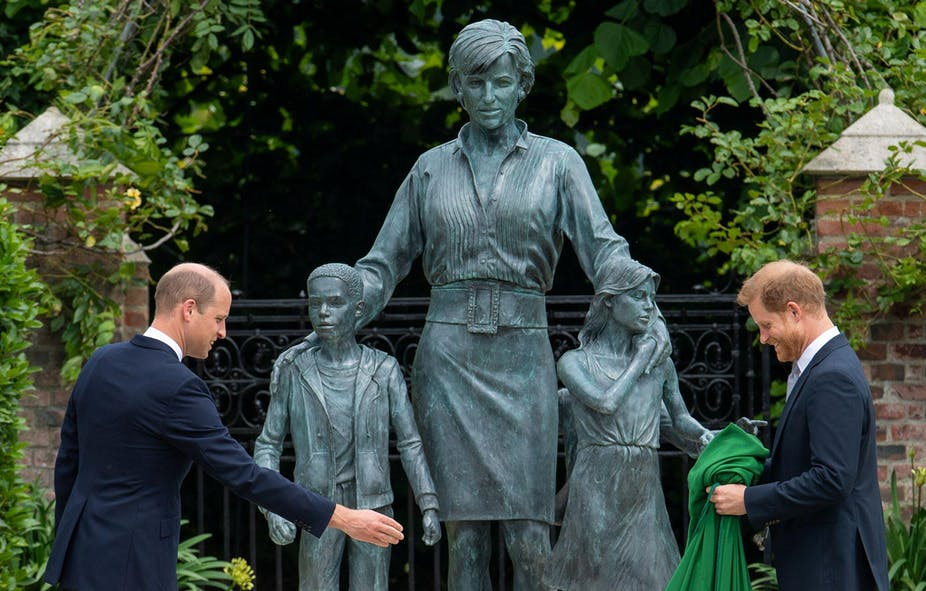 Princes William and Harry stand in front of a statue to their mother, Diana, Princess of Wales.