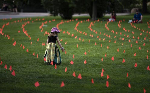Little girl stands amid flags representing children who died at Indian Residential Schools