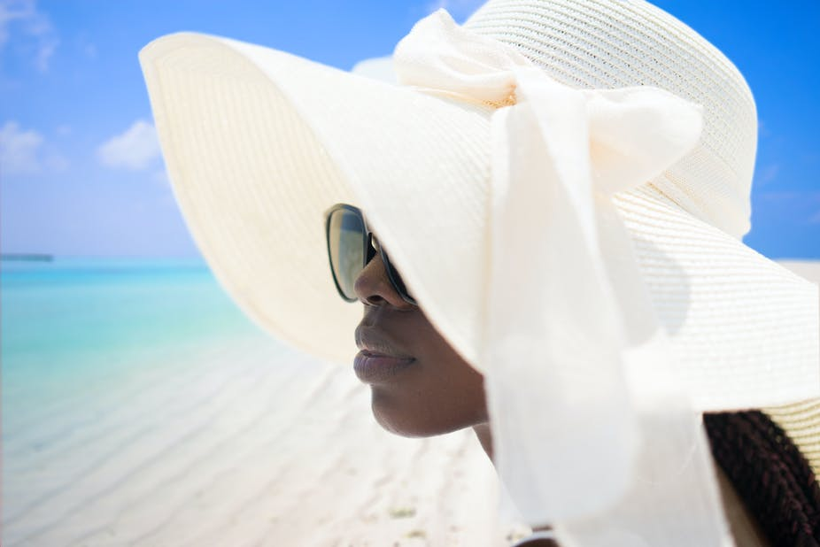 A portrait of woman wearing a summer hat and sunglasses on tropical beach.